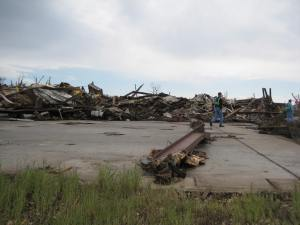This industrial warehouse was completely leveled and partially swept away. Note the crumpled steel beams in the background. Credit: NOAA